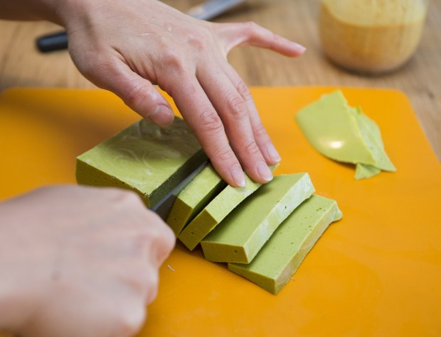 Angela Huang slices a block of zucchini cheese, made with ingredients that follow the Autoimmune Protocol diet.